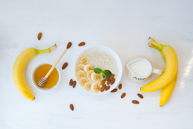 Havermout met honing, banaan en noten in een bord op een witte muur met de rest van de ingrediënten liggen in het midden van het frame. bovenaanzicht.