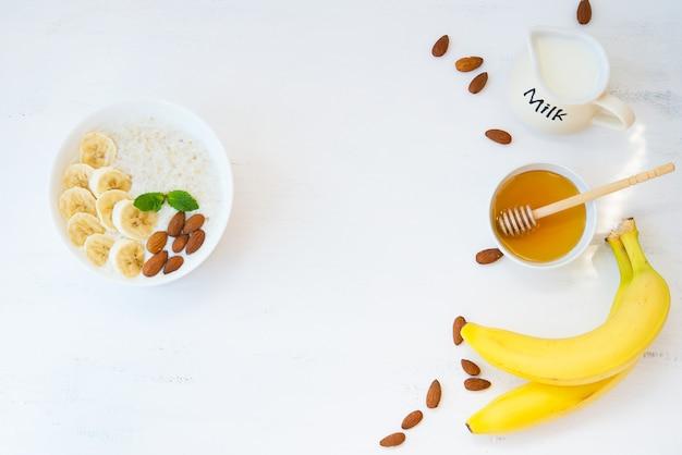 Havermout met honing, banaan en noten in een plaat op een witte muur met de rest van de ingrediënten liggend op een witte muur. bovenaanzicht.