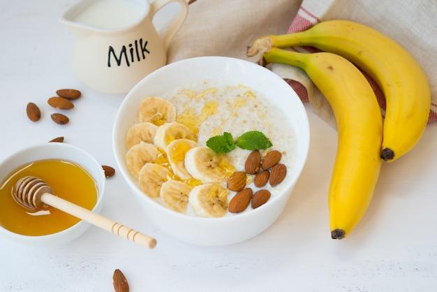 Havermout met honing, banaan en noten in een plaat op een witte muur.