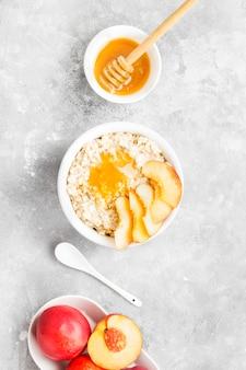 Havermout met nectarine en honing op een grijze achtergrond. bovenaanzicht. voedsel achtergrond. toning