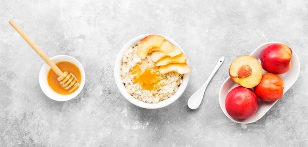 Havermout met nectarine en honing op een grijze achtergrond. bovenaanzicht. voedsel achtergrond
