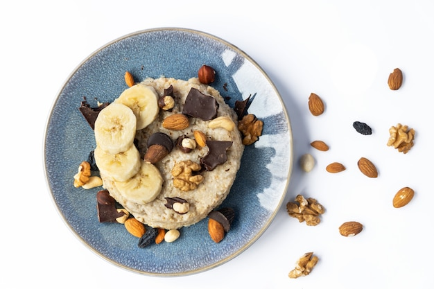 Havermout met noten en chocolade op een blauw bord. goede voeding.
