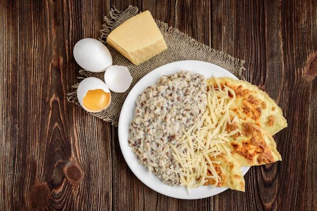 Havermout met omelet en kaas op donkere houten tafel.