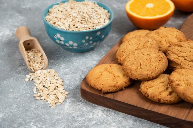 Havermout met zelfgemaakte koekjes over grijze tafel.