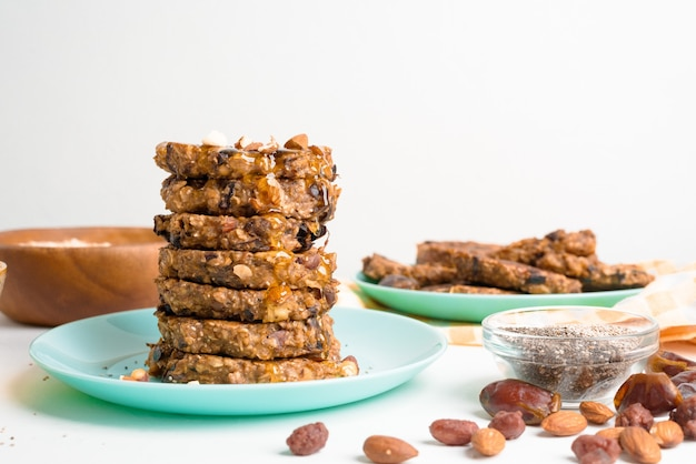 Havermoutbananenpannenkoekjes met chiazaad, amandelen, pruimen en dadels, overgoten met honing en geplette noten