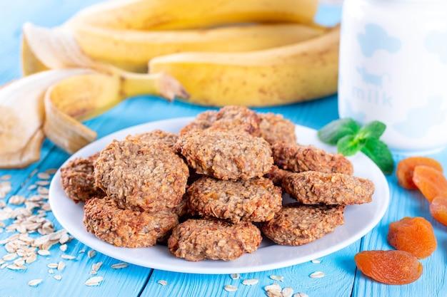 Havermoutgebakje met banaan en gedroogde abrikozen op een blauwe houten achtergrond. gezond ontbijt concept.