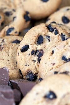 Havermoutkoekjes en grote stukjes zoete chocolade samen, koekjes met stukjes chocolade erin, close-up eten voor desserts