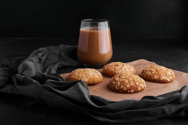 Havermoutkoekjes geserveerd met een glas warme chocolademelk.