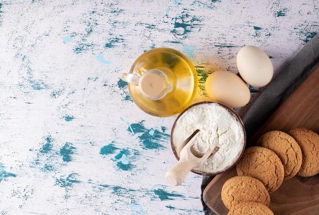 Havermoutkoekjes in een houten schotel met rond ingrediënten.