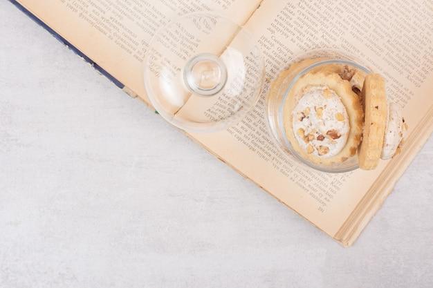 Havermoutkoekjes in glazen pot en op boek.