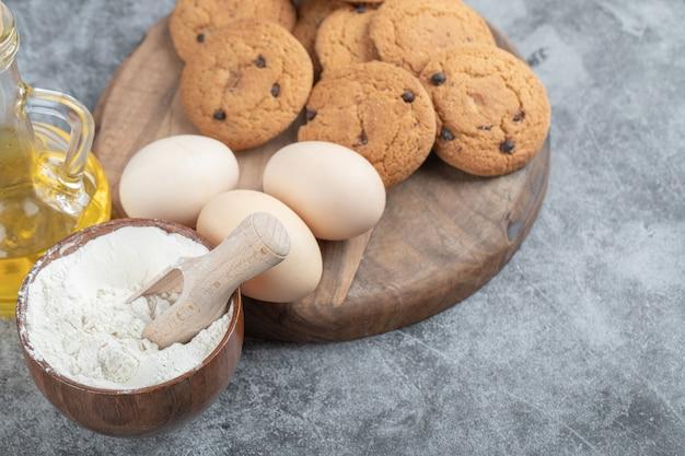 Havermoutkoekjes met chocoladedruppels op een houten bord met ingrediënten eromheen