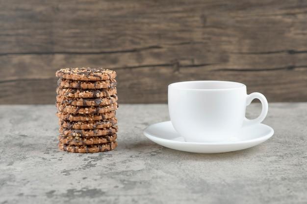 Havermoutkoekjes met chocoladesiroop met een kopje thee op een stenen tafel.
