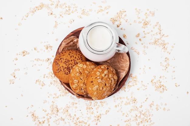 Havermoutkoekjes met melk op wit.