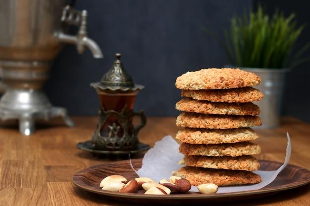 Havermoutkoekjes met noten en thee in samovar op een houten lijst