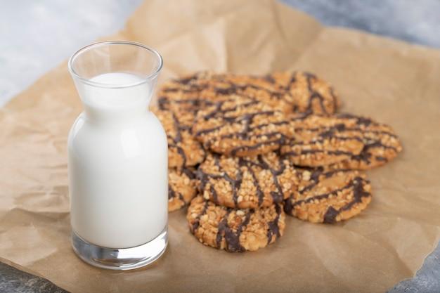 Havermoutkoekjes met zaden en granen met glazen kruik melk.
