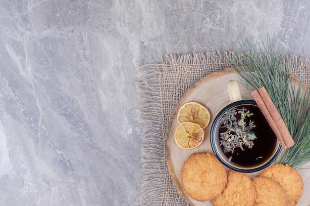Havermoutkoekjes op een houten bord met een kopje glintwine