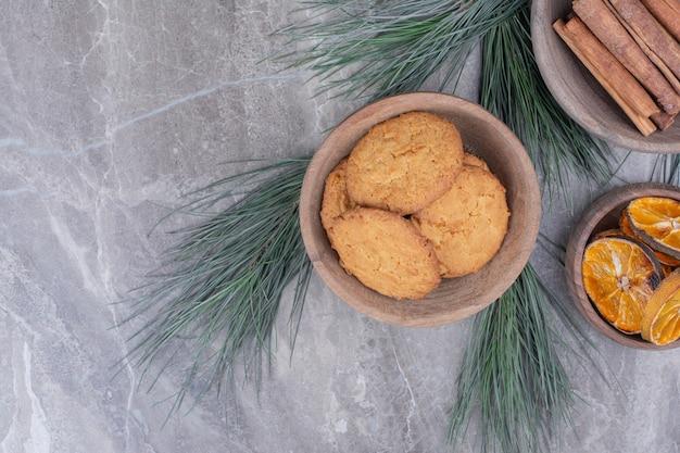Havermoutkoekjes op een houten kop met kaneel en stukjes sinaasappel