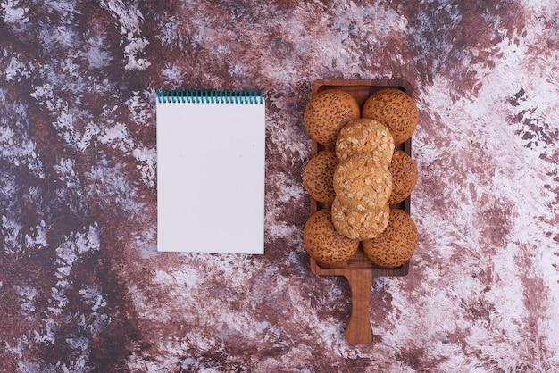Havermoutkoekjes op een houten schaal met een notebok opzij.