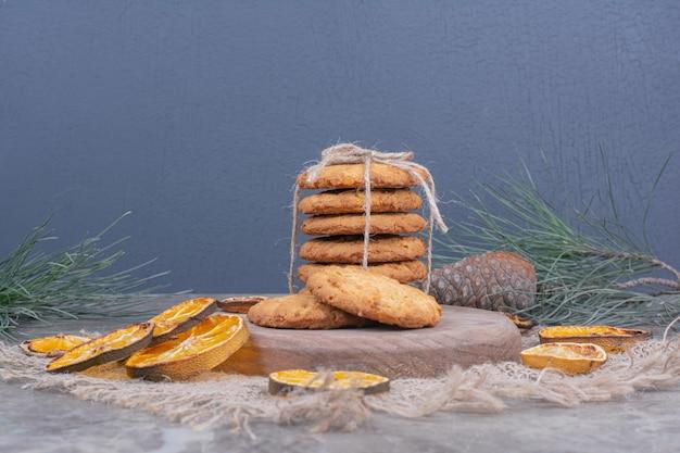 Havermoutkoekjes op een houten schotel met droge stukjes sinaasappel rond
