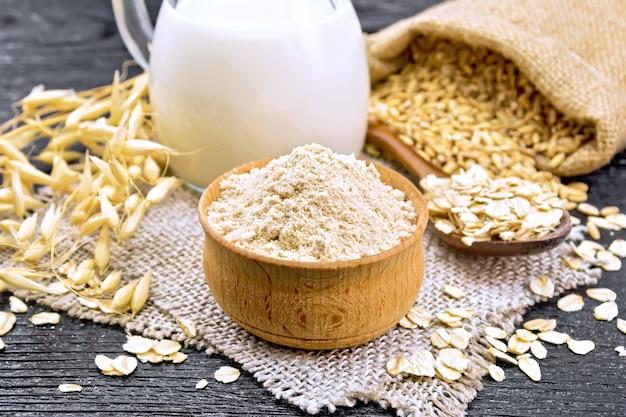 Havermoutmeel in kom, melk in kruik, havermout in lepel op servet van jute, graan in zak, haverstelen tegen donkere houten plank