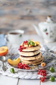 Havermoutpannekoeken met honing, die met bessen en vruchten op een witte houten achtergrond wordt gediend.