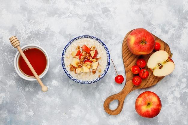 Havermoutpap in een kom met honing en rode appelplakken, bovenaanzicht