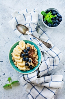 Havermoutpap met banaan, chocolade en verse bosbessen in een kom op een lichtgrijze leisteen, steen of betonnen ondergrond