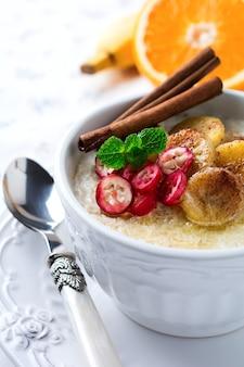 Havermoutpap met gebakken bananen, kaneel, sinaasappel en veenbessen in een ceramische kom op een lichte oppervlakte. selectieve aandacht.