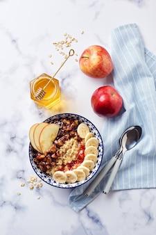 Havermoutpap met gekarameliseerde appels met kaneel, banaan, geraspte aardbeien en honing op lichte marmeren achtergrond, bovenaanzicht.