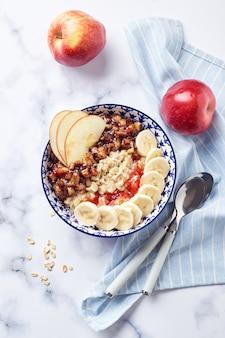 Havermoutpap met gekarameliseerde appels met kaneel, banaan, geraspte aardbeien op lichte marmeren achtergrond, bovenaanzicht.