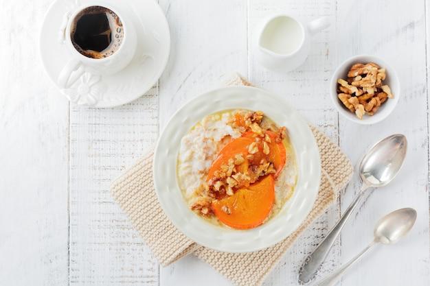 Havermoutpap met gekarameliseerde persimmon en walnoten in een lichte ceramische kom op een witte houten lijst. selectieve aandacht. bovenaanzicht. kopieer ruimte.