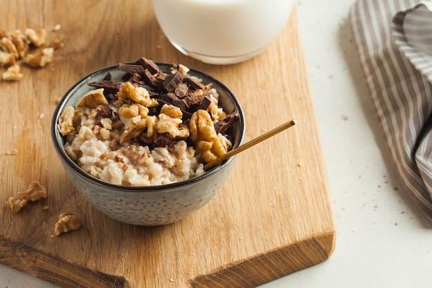 Havermoutpap met noten, chocolade in een grijze kom, een glas melk. ontbijt, gezond eten. goedemorgen.