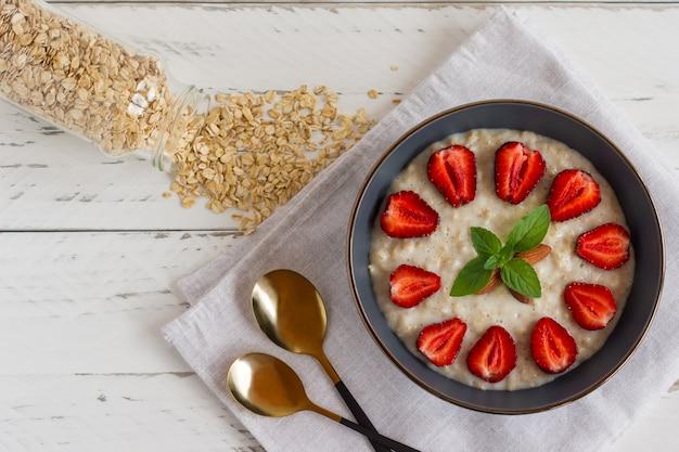 Havermoutpap met plakjes aardbei en vlokken in kom op witte tafel.
