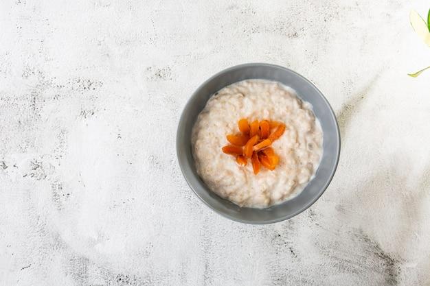 Havermoutpap of havermoutpap of ontbijtgranen met gedroogde abrikozen geïsoleerd op een witte marmeren achtergrond. zelfgemaakt eten. lekker ontbijt. selectieve aandacht. horizontale foto.