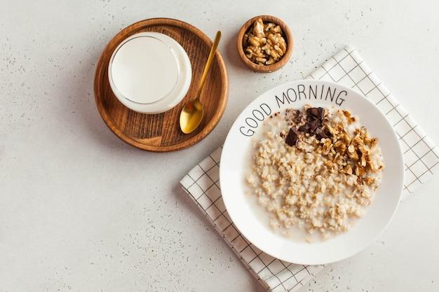 Havermoutpap op een bord met goedemorgen en een kopje melk. gezond eten. ontbijt.