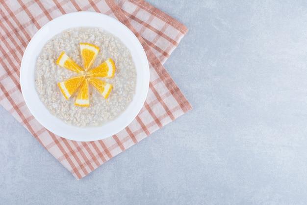 Havermoutschotel met een kleine topping van gehakte sinaasappelplak op marmeren achtergrond.