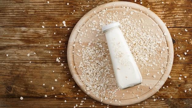 Havervlokken en fles verse melk op een houten bord. houten rustieke achtergrond