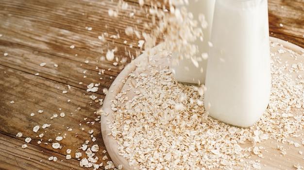 Havervlokken en fles verse melk op een houten bord. houten rustieke achtergrond Premium Foto