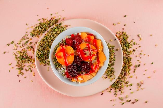 Havervlokken in een kom met pistache, abrikoos, bessen, gelei