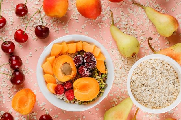 Havervlokken in kommen met peer, sinaasappel, kers, abrikoos, bessen