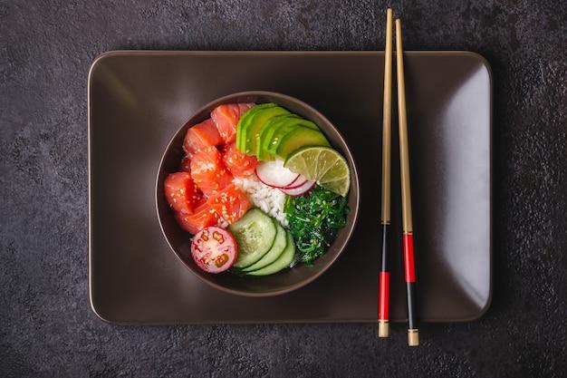 Hawaïaanse zalm poke salade met rijst, groenten en zeewier.
