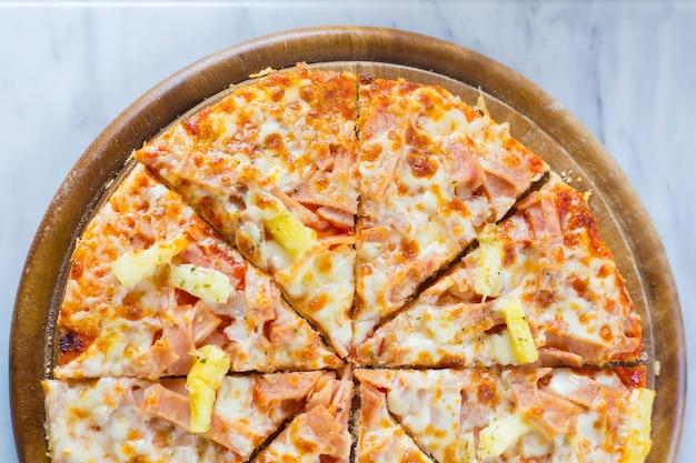 Hawaiiaanse pizza is een italiaans gerecht dat is gemaakt met tomatensaus, gehakte ananas, ham en kaas.