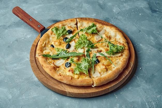Hawaiiaanse pizza met kip, gesmolten kaas en ananas op een houten bord