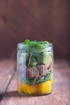 Hawaiiaanse porssalade met tonijn, avocado en groenten in een kruik in het midden op een rustieke lijst