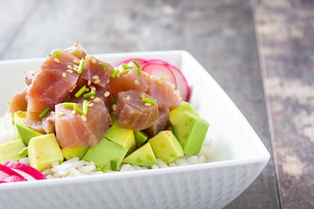 Hawaiiaanse tonijn por kom met avocado, radijs en sesamzaadjes op houten tafel