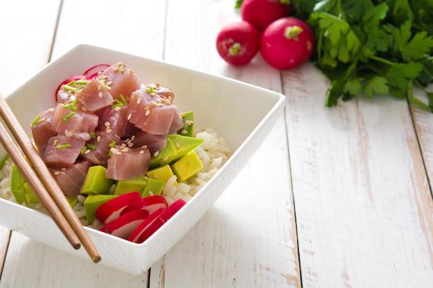Hawaiiaanse tonijn por kom met avocado, radijs en sesamzaadjes op witte houten tafel kopie ruimte