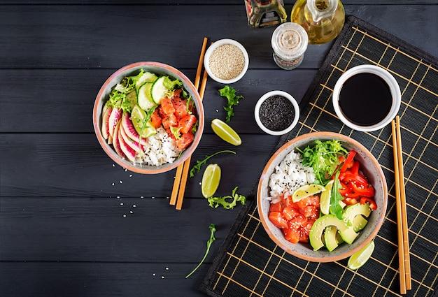 Hawaiiaanse zalmvissen porkom met rijst, avocado, paprika, komkommer, radijs, sesamzaad en limoen.