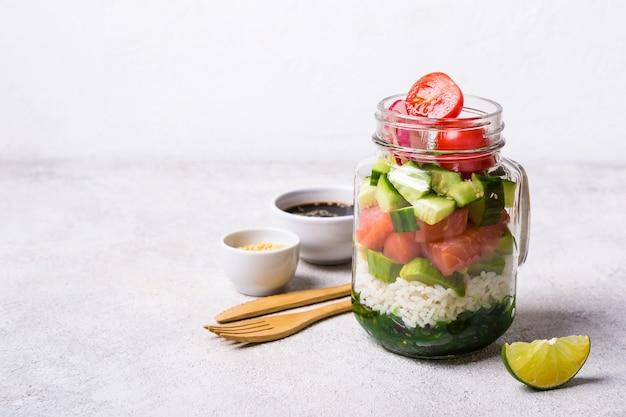 Hawaiiaanse zalmzaksalade in glazen pot met rijst en groenten, selectieve focus.