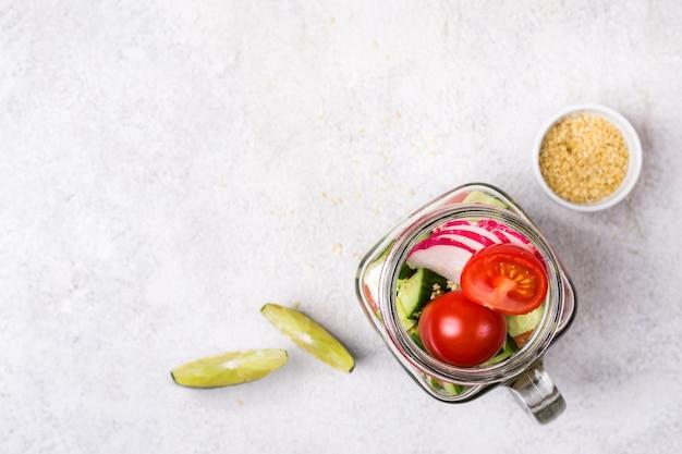 Hawaiiaanse zalmzaksalade met groenten in glazen pot en en limoenschijfjes, selectieve focus.
