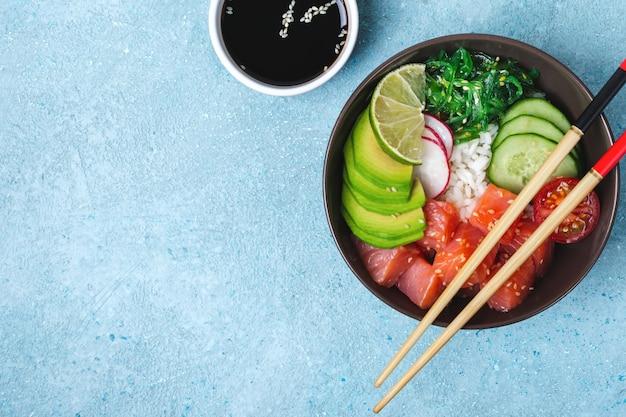 Hawaiiaanse zalmzaksalade met rijst, groenten en zeewier op blauwe achtergrond.